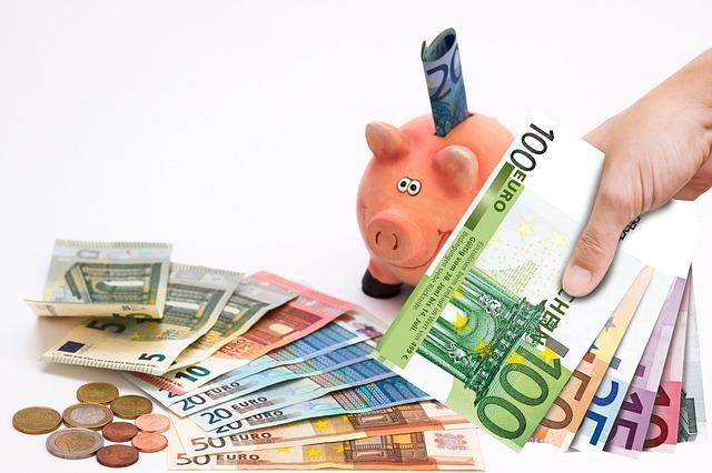 bankovky v ruce, na stole a pokladnička