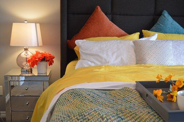 postel, barevné lůžkoviny, noční stolek